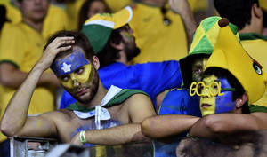 Photo - Brazil supporters react after the World Cup semifinal soccer match between Brazil and Germany at the Mineirao Stadium in Belo Horizonte, Brazil, Tuesday, July 8, 2014. Germany won the match 7-1. (AP Photo/Martin Meissner)