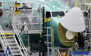 photo - Workers assemble a Boeing Co. next-generation 737 airplane, Tuesday, Jan. 29, 2013 at the company's 737 assembly facility in Renton, Wash. On Jan. 25, 2013, Boeing began assembling next-generation 737 passenger airplanes at an increased rate of 38 planes per month. (AP Photo/Ted S. Warren)