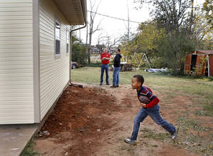 Photo - Deric Jr. carries a football as he runs in the backyard of his family's home after the ceremony. Deric  (cq) and Amanda Isaac and their four children were officially welcomed into their refurbished home near NE 63 and Kelley during a ceremony Saturday morning, Nov. 10, 2012. Their home received extensive repairs and was renovated through Central Oklahoma Habitat for Humanity Veteran Critical Home Repair project. The Home Depot Foundation and local home repair business, Parker Brothers Roofing, were acknowledged for their contributions to the project. Photo by Jim Beckel, The Oklahoman