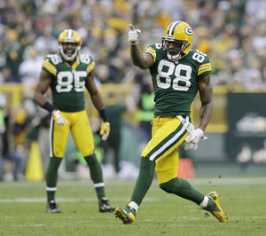 Photo - Green Bay Packers' Greg Jennings (85) watches as Jermichael Finley (88) celebrates a catch during the second half of an NFL football game against the Minnesota Vikings Sunday, Dec. 2, 2012, in Green Bay, Wis. The Packers won 23-14. (AP Photo/Morry Gash)