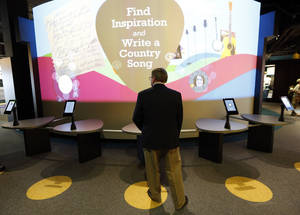 Photo - In this April 10, 2014, photo, a visitor looks at an exhibit in a new section of the Country Music Hall of Fame and Museum in Nashville, Tenn. A $100 million expansion has added more than 200,000 square feet of space to the existing building. (AP Photo/Mark Humphrey)