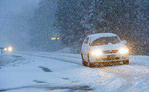 Photo - Vehicles slowly make their way on a snow-covered Alabama state Route 35, on Tuesday, Feb. 11, 2014, in Fort Payne, Ala. Residents woke to a blanket of snow that was expected to continue throughout the morning hours. (AP Photo/Hal Yeager)