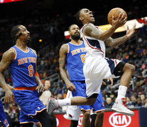 Photo - Atlanta Hawks point guard Jeff Teague, right, drives past New York Knicks shooting guard J.R. Smith (8) and center Tyson Chandler (6) to score in the first half of an NBA basketball game Saturday, Feb. 22, 2014, in Atlanta. (AP Photo/John Bazemore)
