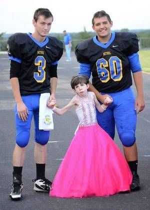 Photo - Brytni Srader is escorted by her cousin, Travis Sullivan (3), and her brother, Brady Sullivan (60), as she arrives. (Shawnee News-Star photo)