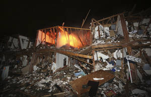 Photo - A fire still burns in a apartment complex destroyed near a fertilizer plant that exploded earlier in West, Texas, in this photo made early Thursday morning, April 18, 2013.  (AP Photo/LM Otero)