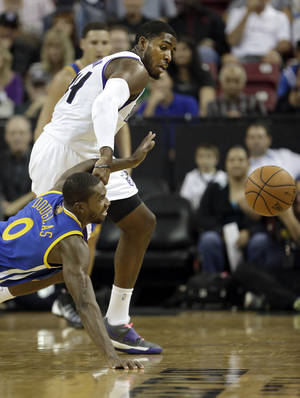 Photo - Golden State Warriors guard Toney Douglas, bottom, and Sacramento Kings forward Jason Thompson scramble after the ball during the first quarter of an NBA preseason basketball game in Sacramento, Calif., Wednesday, Oct. 23, 2013. (AP Photo/Rich Pedroncelli)