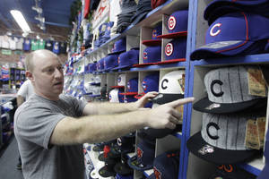 Photo -   Brad Rosen points to the Chicago Cubs' home, left, and away, right, ball caps from the team's last world championship season in 1908, at Sports World near Wrigley Field, Thursday, Sept. 27, 2012, in Chicago. Even for a team with a record of futility unmatched in professional baseball and, heck, all of professional sports, this season has been one of the most dismal in Cubs history. About the only good thing that could be said about a team poised to lose 100 games for the first time in 46 years--one of which came after the shortstop trotted off the field thinking there were three outs instead of two--is that it is doing so in front of fewer fans than any year in the last decade. (AP Photo/M. Spencer Green)