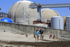 Photo -   FILE - In this June 30, 2011 file photo, beach-goers walk on the sand near the San Onofre nuclear power plant in San Clemente, Calif. A report commissioned by an environmental group warned Tuesday, May 15, 2012 that running California's San Onofre nuclear plant at reduced power would not resolve problems with badly worn tubing that have kept its twin reactors offline for more than three months, and might make it worse. (AP Photo, Lenny Ignelzi, File)