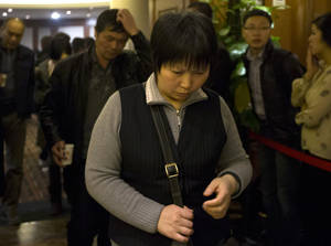 Photo - Chinese relatives of passengers aboard a missing Malaysia Airlines plane walk out from a hotel room after attending a briefing by Malaysia Airlines in Beijing, China Sunday, March 16, 2014. Attention focused Sunday on the pilots of the missing Malaysia Airlines flight after the country's leader announced findings so far that suggest someone with intimate knowledge of the Boeing 777's cockpit seized control of the plane and sent it off-course. (AP Photo/Andy Wong)