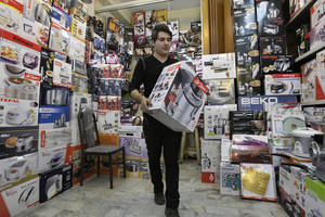 photo -   Iranian shopkeeper Masoud Hatami works at a home appliance store in Tehran, Iran, Thursday, Nov. 8, 2012. Sanctions-hit Iran has banned the import of foreign-made cars, laptops, and other 'luxury' goods in the hope of saving billions of dollars in hard currency, a state-owned newspaper reported Thursday. IRAN daily listed 75 products, from watches, home appliances and cell phones to coffee and toilet paper, that it said could no longer be purchased from abroad. But it says the ban does not apply to components used to produce the products. Iranian firms assemble many products including watches, laptops and cell phones. (AP Photo/Vahid Salemi)