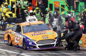 Photo - Joey Logano's crew works on his car after he crashed into the wall during the NASCAR Sprint Cup Series auto race at New Hampshire Motor Speedway on Sunday, July 13, 2014, in Loudon, N.H. The crash took Logano out of the race. Brad Keselowski won. (AP Photo/Jim Cole)