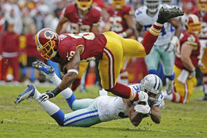 Photo - Washington Redskins wide receiver Pierre Garcon is upended by Dallas Cowboys cornerback Orlando Scandrick during the first half of an NFL football game in Landover, Md., Sunday, Dec. 22, 2013. (AP Photo/Alex Brandon)