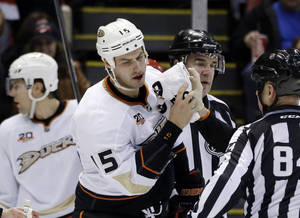Photo - Anaheim Ducks center Ryan Getzlaf (15) is helped off the ice after being boarded by Detroit Red Wings defenseman Kyle Quincey during the first period of an NHL hockey game in Detroit, Tuesday, Dec. 17, 2013. (AP Photo/Carlos Osorio)