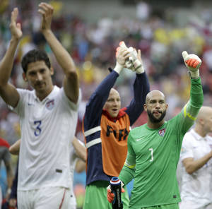 Photo - United States' goalkeeper Tim Howard (1) and his teammates celebrate after qualifying for the next World Cup round following their 1-0 loss to Germany during the group G World Cup soccer match between the USA and Germany at the Arena Pernambuco in Recife, Brazil, Thursday, June 26, 2014. (AP Photo/Ricardo Mazalan)