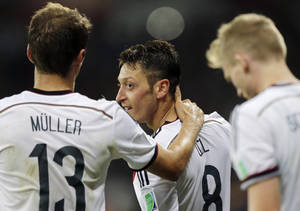 Photo - Germany's Mesut Ozil celebrates after scoring his side's second goal in extra time with teammate Thomas Mueller during the World Cup round of 16 soccer match between Germany and Algeria at the Estadio Beira-Rio in Porto Alegre, Brazil, Monday, June 30, 2014. Germany defeated Algeria 2-1 to advance to the quarterfinals.  (AP Photo/Matthias Schrader)