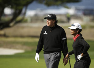 Photo - Phil Mickelson, left, talks with former United States Secretary of State Condoleezza Rice while walking up the 12th fairway of the Monterey Peninsula Country Club Shore Course during the first round of the AT&T Pebble Beach Pro-Am golf tournament Thursday, Feb. 6, 2014, in Pebble Beach, Calif. (AP Photo/Eric Risberg)