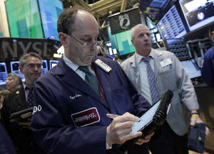 Photo - In this  April 24, 2013, photo, Trader Gordon Charlop, center, works on the floor of the New York Stock Exchange. World stock markets mostly rose Monday April 29, 2013 as weaker-than-expected U.S. growth added to expectations that central banks will continue easy monetary policies to support economic recovery. (AP Photo/Richard Drew)