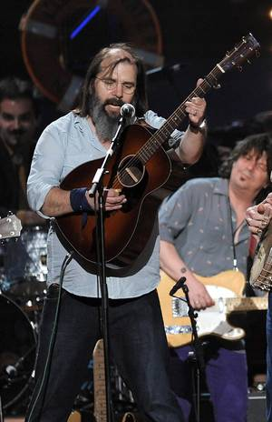 "Photo -   FILE - In this May 3, 2009 file photo, musician Steve Earle performs at a benefit concert celebrating Pete Seeger's 90th birthday at Madison Square Garden in New York. Earle has released a CD and his debut novel with the same titles, ""I'll Never Get Out of This World Alive."" (AP Photo/Evan Agostini, file)"