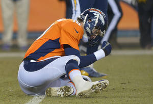 Photo - Denver Broncos quarterback Peyton Manning (18) pounds his fist on the ground after throwing an interception against the San Diego Chargers in the fourth quarter of an NFL football game, Thursday, Dec. 12, 2013, in Denver. San Diego won 27-20. (AP Photo/Jack Dempsey)