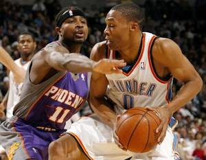 photo - The Thunder's  Russell  Westbrook (0) drives past Phoenix's Dee Brown (11) during the second half of the NBA basketball game between the Oklahoma City Thunder and the Phoenix Suns at the Ford Center on, Monday, Dec. 29, 2008, in Oklahoma City, Okla. Photo by CHRIS LANDSBERGER, THE OKLAHOMAN