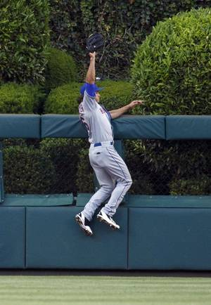 Photo - New York Mets center fielder Matt den Dekker leaps to catch the fly ball by Philadelphia Phillies' Ryan Howard during the second inning of a baseball game, Monday, June 2, 2014, in Philadelphia. (AP Photo/Chris Szagola)