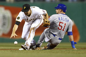 Photo - Pittsburgh Pirates shortstop Jordy Mercer, left, drops the ball and Chicago Cubs' Ryan Kalish (51) is safe at second on a ground ball by Edwin Jackson in the fifth inning of a baseball game Wednesday, April 2, 2014, in Pittsburgh. A throwing error was ruled on Pirates third baseman Pedro Alvarez. (AP Photo/Keith Srakocic)