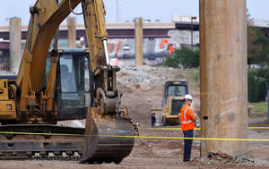 Photo - An industrial accident near the old Interstate 40 proved deadly for a construction worker, Thursday. Officials say the man was pinned between a trailer and excavation equipment after helping unload an I-beam from the bridge.  Photos by Jim Beckel, The Oklahoman