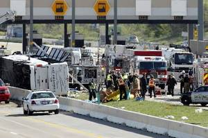Photo - First responders are on the scene of a Cardinal Coach Line charter bus accident on Hwy. 161 in Irving, Texas on Thursday morning, April 11, 2013. Authorities say at least two people are dead and several injured after the chartered bus overturned. (AP Photo/The Dallas Morning News, Tom Fox)