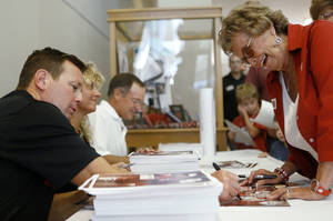 Photo - Oklahoma football coach Bob Stoops, signs a poster for Bobbie Humphreys of Oklahoma CIty during the Sooner Caravan stop at the National Cowboy & Western Heritage Museum  in Oklahoma City, Wednesday, August 1, 2012. Photo by Bryan Terry, The Oklahoman
