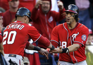 Photo -   Washington Nationals' Ian Desmond, left, and Michael Morse celebrate after scoring on a two-RBI single by Tyler Moore during the eighth inning in Game 1 of baseball's National League division series against the St. Louis Cardinals, Sunday, Oct. 7, 2012, in St. Louis. (AP Photo/Jeff Roberson)