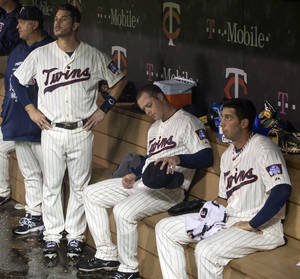 Photo - Minnesota Twins starting pitcher Andrew Albers, center, sits in the dugout with teammates Trevor Plouffe, left, and Chris Colabello, right, during a fourth inning rain delay of a baseball game against the Tampa Bay Rays, Saturday, Sept. 14, 2013, in Minneapolis. (AP Photo/Paul Battaglia)