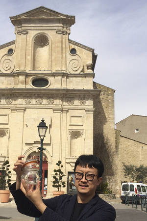 Photo - In this photo taken on March 29, 2014, Beijing artist Liang Kegang collects fresh air in the commune of Forcalquier in Provence, France. The jar of air is a piece of conceptual art to protest his home city's choking pollution. It has fetched $860 in a small auction. (AP Photo/Liang Kegang)