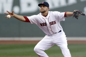 Photo - Boston Red Sox third baseman Brandon Snyder bare-hands a grounder by San Diego Padres' Carlos Quentin, who reached first with a single during the first inning of an interleague baseball game at Fenway Park in Boston, Wednesday, July 3, 2013. (AP Photo/Elise Amendola)
