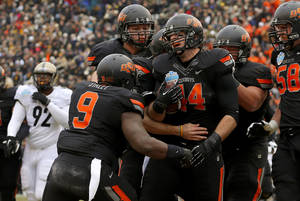 photo - Oklahoma State's Jeremy Seaton (44) celebrates with teammates after a touchdown during the Heart of Dallas Bowl football game between Oklahoma State University and Purdue University at the Cotton Bowl in Dallas, Tuesday, Jan. 1, 2013. Oklahoma State won 58-14. Photo by Bryan Terry, The Oklahoman