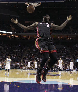 Photo - Miami Heat's LeBron James (6) reacts after dunking against the Charlotte Bobcats during the first half of an NBA basketball game in Charlotte, N.C., Saturday, Nov. 16, 2013. (AP Photo/Chuck Burton)