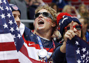 Photo - U.S. fans cheer as Russia and the USA take the ice before playing in a men's ice hockey game at the 2014 Winter Olympics, Saturday, Feb. 15, 2014, in Sochi, Russia. (AP Photo/Mark Humphrey)