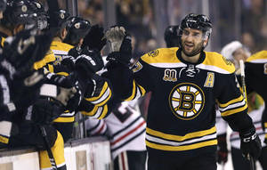 Photo - Boston Bruins center Patrice Bergeron, right, is congratulated by teammates after his goal against the Chicago Blackhawks during the first period of an NHL hockey game, Thursday, March 27, 2014, in Boston. (AP Photo/Charles Krupa)