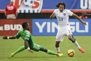 Photo - Nigeria's Ogenyi Onazi, left, tries to take the ball from United States's Jermaine Jones (13) during the second half of an international friendly soccer match in Jacksonville, Fla., Saturday, June 7, 2014. The United States won 2-1. (AP Photo/John Raoux)