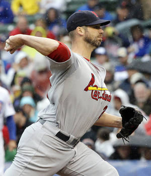 photo -   As rain falls, St. Louis Cardinals starter Chris Carpenter throws against the Chicago Cubs during the first inning of a baseball game in Chicago, Friday, Sept. 21, 2012. (AP Photo/Nam Y. Huh)