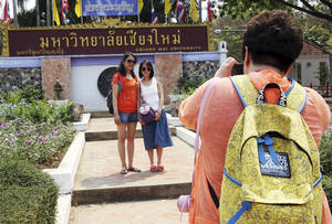 "Photo - In this March 30, 2014 photo, Chinese tourists pose for a photograph at the main entrance to Chiang Mai University in Chiang Mai province, northern Thailand. The bucolic, once laid-back campus of one of Thailand's top universities is under a security clampdown. Not against a terrorist threat, but against Chinese tourists. Thousands have clambered aboard student buses at the university, made a mess in cafeterias and sneaked into classes to attend lectures. Someone even pitched a tent by a picturesque lake. The reason: ""Lost in Thailand,"" 2012 slapstick comedy partly shot on campus that is China's highest-grossing homegrown movie ever. (AP Photo/Apichart Weerawong)"