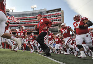 Photo -   Nebraska's retiring athletic director and former coach Tom Osborne runs onto the field with players prior to an NCAA college football game against Minnesota, in Lincoln, Neb., Saturday, Nov. 17, 2012. Osborne is being honored for his involvement in 500 Nebraska football games. (AP Photo/Dave Weaver)