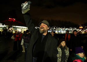 photo - John Sanders, the chair of the music department at Edmonds Community College, holds up an ounce of marijuana as hundreds gathered at a smoke in to celebrate legalization of marijuana in Washington Thursday, Dec. 6, 2012, at the Seattle Center International Fountain. Sanders said he wasn't smoking that night, but wanted to demonstrate his right to carry. (AP Photo/Colin Diltz, The Seattle Times)