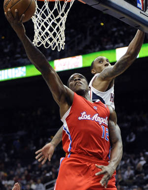 Photo -   Los Angeles Clippers' Eric Bledsoe (12) scores over Atlanta Hawks' Jeff Teague (0) in the second half of an NBA basketball game at Philips Arena in Atlanta, Saturday, Nov. 24, 2012. Atlanta won 104-93. (AP Photo/David Tulis)