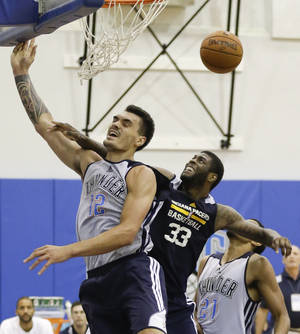 Photo - Oklahoma City Thunder's Steven Adams (12) is fouled by Indiana Pacers' Willie Reed (33) as he goes up for a shot during an NBA summer league basketball game in Orlando, Fla., Wednesday, July 9, 2014. (AP Photo/John Raoux)