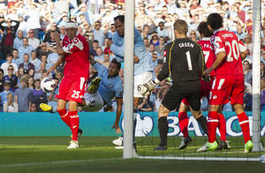 Photo -   Manchester City's Carlos Tevez, bottom 2nd left, sets up teammate Yaya Toure's goal against Queens Park Rangers during their English Premier League soccer match at The Etihad Stadium, Manchester, England, Saturday, Sept. 1, 2012. (AP Photo/Jon Super)