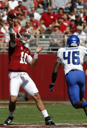 Photo - Alabama quarterback AJ McCarron (10) throws a pass while under pressure from Georgia State linebacker Jarrell Robinson (46) during the first half of an NCAA college football game on Saturday, Oct. 5, 2013, in Tuscaloosa, Ala. (AP Photo/Butch Dill)