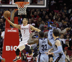 Photo - Houston Rockets guard Jeremy Lin (7) drives for a reverse layup past Memphis Grizzlies' Ed Davis (32) and Zach Randolph (50) during the first half of an NBA basketball game Thursday, Dec. 26, 2013, in Houston. (AP Photo/Bob Levey)
