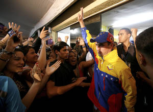Photo - Miranda State's Gov. Henrique Capriles, right, greets his supporters after being re-elected during an elections in Caracas, Venezuela, Sunday, Dec. 16, 2012. Capriles lost to Chavez in the country's October election, and his re-election Sunday will allow him to cement his position as Venezuela's dominant opposition leader, even as other opposition candidates floundered. (AP Photo/Fernando Llano)