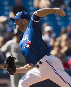 Photo - Toronto Blue Jays starter J.A. Happ pitches to the Tampa Bay Rays during the first inning of a baseball game in Toronto, Saturday, Sept. 28, 2013. (AP Photo/The Canadian Press, Mark Blinch)
