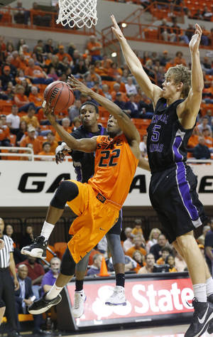 Photo - Oklahoma State guard Markel Brown shoots between Central Arkansas guard Ryan Williams (5) and forward Jordan Harks (15) during the first half of an NCAA college basketball game in Stillwater, Okla., Sunday, Dec. 16, 2012. (AP Photo/Sue Ogrocki)